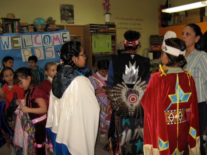 Students relax and chatter after engaging exhibition on Native American dancing.